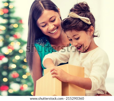 holidays, presents, christmas, xmas concept - happy mother and child girl with gift box - stock photo