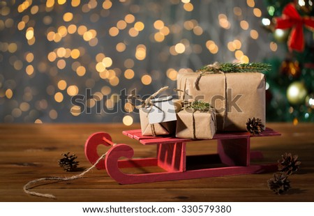 holidays, presents, new year and celebration concept - close up of gift boxes with blank note on red wooden sleigh over christmas tree and lights background
