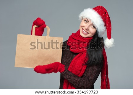 Holidays sale, shopping, Christmas concept. Portrait of smiling woman wearing Santa hat showing shopping bag with empty copy space - stock photo