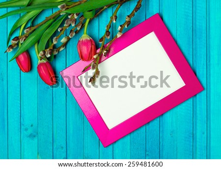 Holidays, still life concept. Easter and spring decoration with tulips, willow branch and card on a wooden table. Selective focus, copy space, top view - stock photo