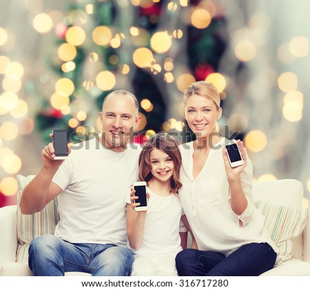 holidays, technology, advertisement and people concept - smiling family with smartphones over living room and christmas tree background - stock photo