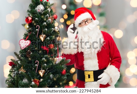 holidays, technology and people concept - man in costume of santa claus with smartphone and christmas tree over lights background - stock photo