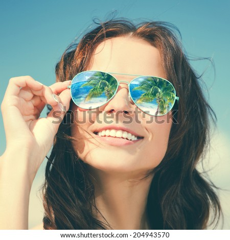 holidays, travel, vacation and happiness concept - beautiful woman in sunglasses with beach reflection - stock photo