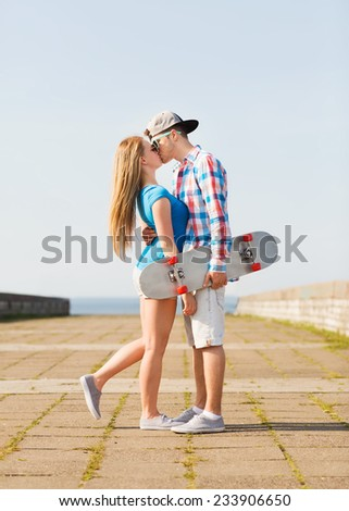 holidays, vacation and love concept - couple with skateboard kissing outdoors - stock photo