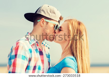 holidays, vacation and love concept - teenage couple kissing outdoors - stock photo