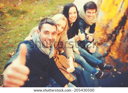 holidays, vacation, happy people concept - group of friends or couples having fun and showing thumbs up in autumn park - stock photo