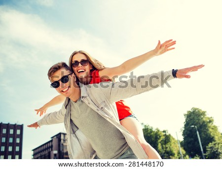 holidays, vacation, love and friendship concept - smiling couple having fun in city - stock photo