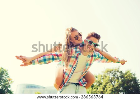 holidays, vacation, love and friendship concept - smiling couple having fun in park - stock photo