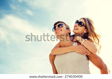 holidays, vacation, love and friendship concept - smiling couple having fun over sky background - stock photo