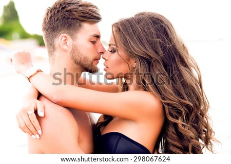holidays,vacation,love and friendship concept - smiling couple having fun over sky background,sunset back light on the beach,kissing happy couple in love Dating interracial couple embracing on date - stock photo