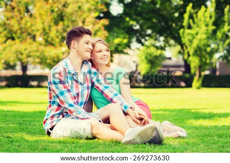 holidays, vacation, love and friendship concept - smiling couple sitting on grass in park - stock photo