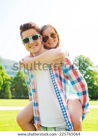 holidays, vacation, love and friendship concept - smiling teen couple in sunglasses having fun in summer park - stock photo