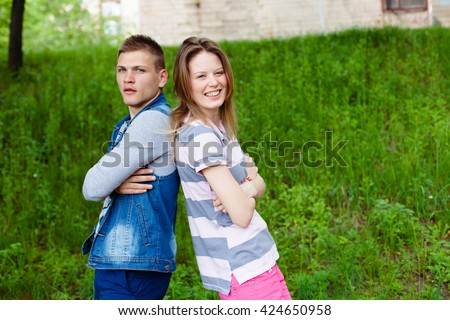 holidays, vacation, love and friendship concept - smiling teen couple young cheerful hipster Best Friends boy and girl having fun, played outdoors, mimic fight, positive emotions, back to back - stock photo