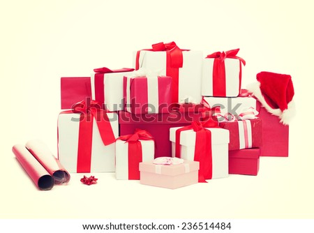 holidays, winter, birthday and celebration concept - christmas presents, decoration paper and santa helper hat - stock photo
