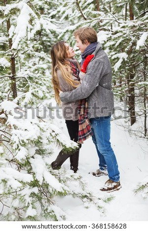 holidays, winter, christmas, love and people concept - happy couple looking on each other in forest among a lot of fir trees in snow