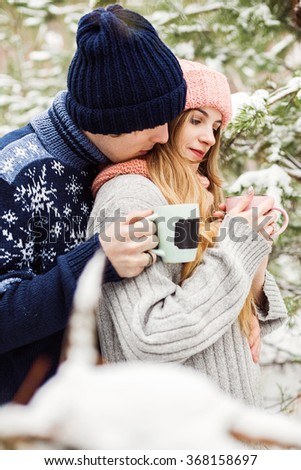 holidays, winter, christmas, love, hot drinks and people concept - beautiful couple with hot tea in cups in forest among fir trees in snow