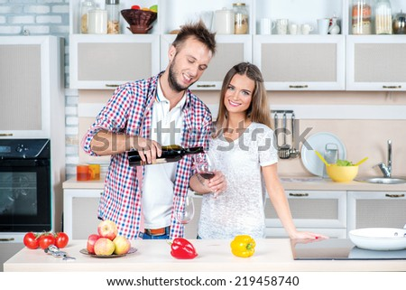 Holidays with wine. Attractive couple in love opens the wine in the kitchen while they cook dinner for a romantic evening. Man pours wine into a glass - stock photo