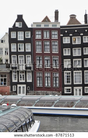Holland, Amsterdam, the facade of old private stone houses downtown and ferryboats