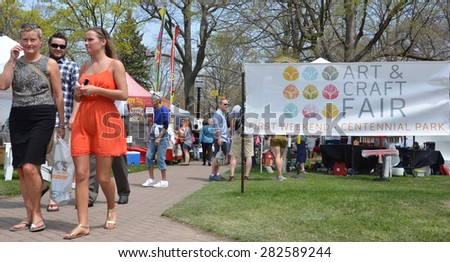 HOLLAND, MI - MAY 3: Patrons enjoy the Tulip Time Festival Art Fair in Holland, MI May 3, 2015.  - stock photo