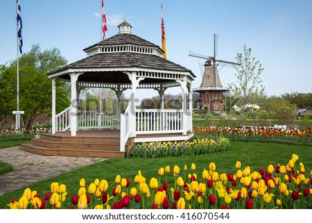 HOLLAND, MICHIGAN-MAY 07, 2015: A gazebo and an authentic wooden windmill from the Netherlands rises behind a field of tulips in Holland Michigan at Springtime. - stock photo