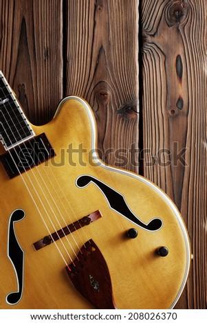 hollow body jazz guitar on aged wood - stock photo