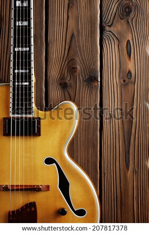 hollow body jazz guitar on aged wood background - stock photo