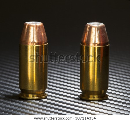 Hollow point bullets on top of cartridges for a forty five caliber handgun - stock photo