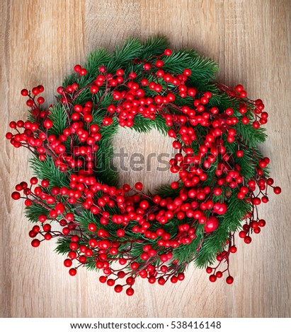 Holly berry Christmas wreath on wooden background