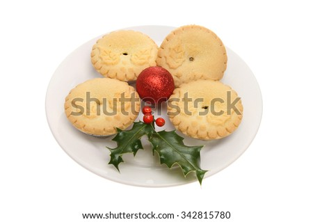 Holly decorated mince pies with a Christmas bauble and a sprig of holly on a plate isolated against white - stock photo