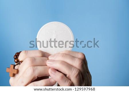 holly Eucharist with rosary - stock photo