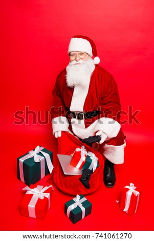 Holly jolly x mas noel! Busy santa in headwear, costume, black belt, shoes, white gloves fills sack with a lot of gifts for kids, with ribbon tapes bows, digital devices, electronics, playstation