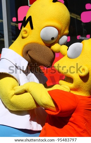 HOLLYWOOD CA - FEBRUARY 14: Homer and Bart Simpson waiting for Matt Groening at his Walk of Fame ceremony where he received his star February 14, 2012 Hollywood, CA. - stock photo