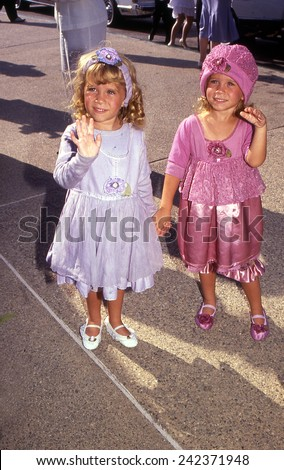 HOLLYWOOD, CALIFORNIA - Exact date unknown - circa 1990 - Mary Kate and Ashley Olsen arriving at a celebrity event - stock photo