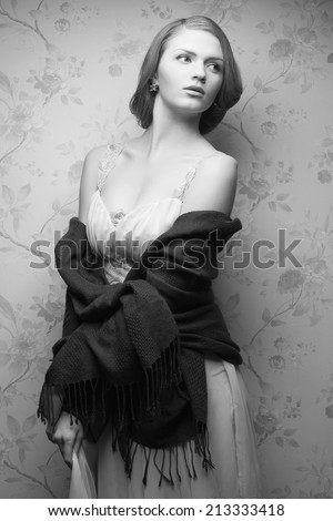 Hollywood diva concept. Vintage portrait of glamorous young actress posing in great dress with seductive neckline and shawl. Great hairdo. Retro style. Studio shot - stock photo