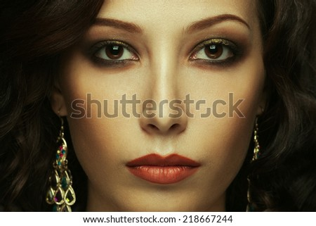Hollywood diva's look concept. Portrait of fashionable model with curly hair and evening make-up posing. Golden earrings. Perfect healthy skin. Superstar style. Close up. Studio shot - stock photo
