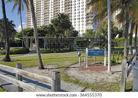 Hollywood, FL, USA - December 14, 2014: Small Harry Berry Park and sign with some sitting areas and restrooms. A tall multi-family building rises up behind Harry Berry Park.