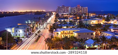 Hollywood Florida, USA. Night panorama of hotels, buildings and moving traffic by the beach with ocean in the background