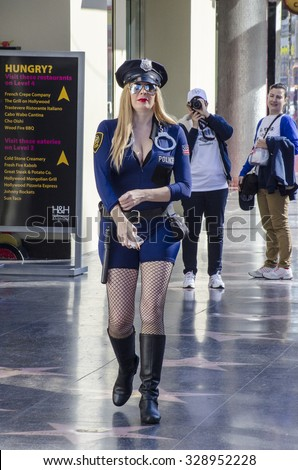 Hollywood, Los Angeles, California, USA - November 6, 2013: A girl dressed as a policeman on Hollywood Boulevard. - stock photo