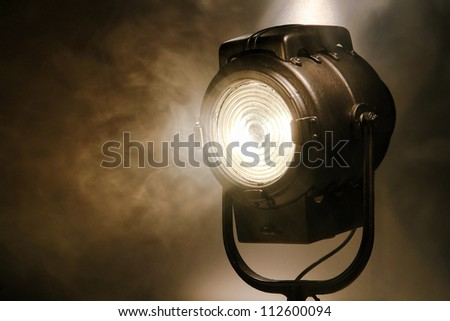 Hollywood old movie studio vintage Fresnel style halogen hot spot light in smoke in sepia - stock photo