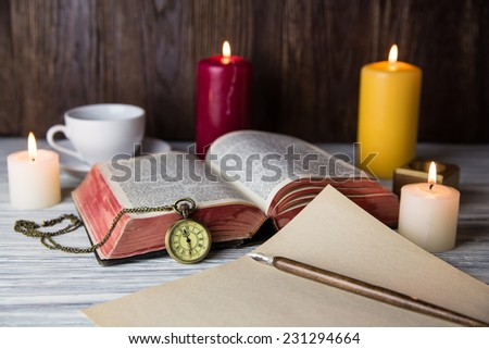 Holy Bible and candle on wood background - stock photo