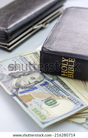 Holy Bible and money. Black wallet