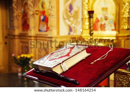 Holy Bible and Orthodox cross prepared for christening ceremony in russian church - stock photo