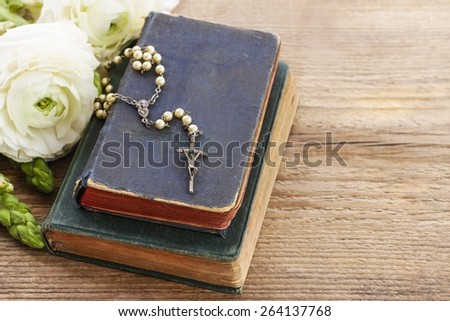 Holy Bible and white rosary. White persian buttercup flowers (ranunculus) in the background, copy space - stock photo