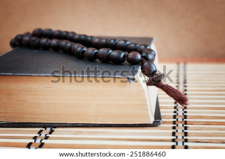 Holy Bible and wooden rosary on a table - stock photo