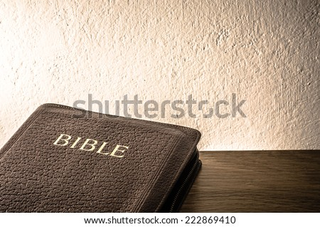 Holy Bible on a table against a raw creamy wall. Background concept with large copy space available. / Bible background