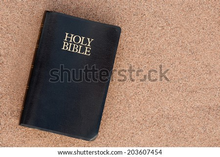 Holy Bible on sand. - stock photo
