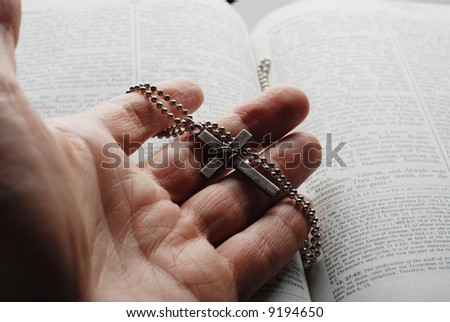 holy bible open with a cross on a hand