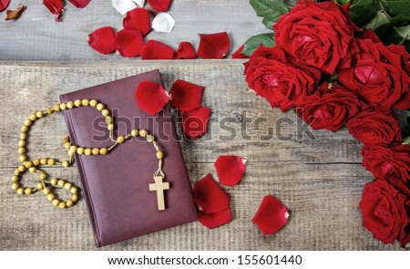 Holy Bible, rosary and stunning red roses on wooden table - stock photo