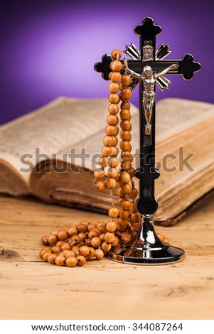 holy book  rosary and crucifix on wooden table - stock photo