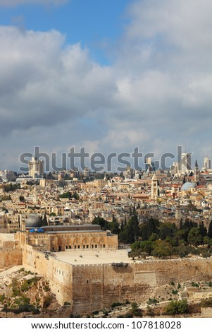 Holy City of Jerusalem. The magnificent panorama of the city. Omar Mosque and the Dome of the Holy Sepulcher. In the background - modern skyscrapers and cranes newly
